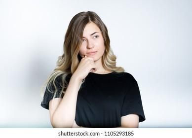 beautiful blond girl thinks, isolated studio photo on background