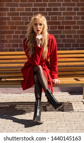 A beautiful blond girl wearing a red coat and gloves is sitting and resting on a street bench near a brick wall. Fashion, commercial, advertising design. Copy space.