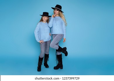 Beautiful blond girls, mother with daughter in autumn winter clothing on a blue background in the studio.