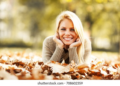 Beautiful blond hair woman lies down on leaves at the park on beautiful autumn day.