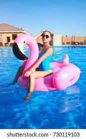 A beautiful blond with a beautiful haircut, in a bright swimsuit on the background of the pool sits on a flamingo. sexy girl in the pool on an inflatable pink flamingo in a bathing suit