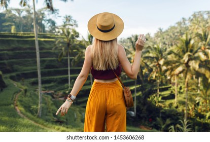 Beautiful  blond  lady in  straw hat from back . Girl walk at typical Asian hillside with rice farming, mountain shape green cascade rice field terraces paddies. Ubud, Bali, Indonesia.