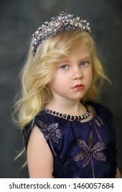Beautiful Blond Little Girl in Crown over dark background