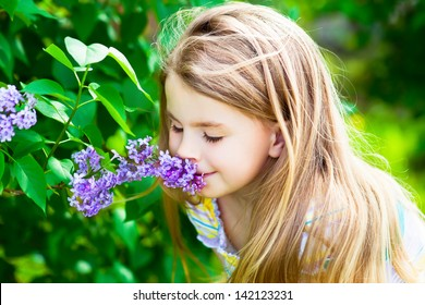 Beautiful blond little girl with long hair smelling flower