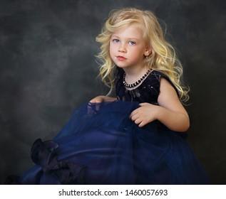 beautiful blond little girl in navy blue dress