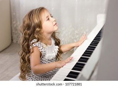 beautiful blond little girl playing near a piano in a white room