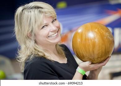 Beautiful blond mature smiling woman with bowling ball.