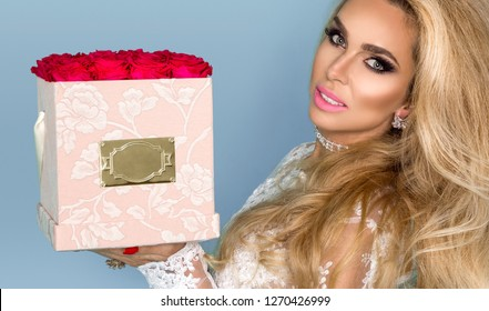 Beautiful blond model in elegant dress holding a bouquet of roses, flower box. Valentine's and birthday gift on a blue background.