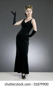 beautiful blond model with fifties glamour look, deep red lipstick, black dress