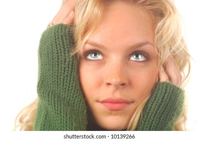 Beautiful blond model in green sweater on a white background.