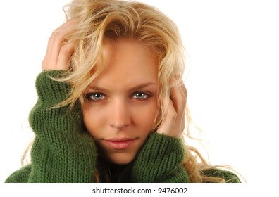 Beautiful blond model in green sweater on a white background with copyspace.
