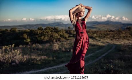 Schönes blondes Modell in der Natur bei Sonnenuntergang in einem roten Kleid gekleidet