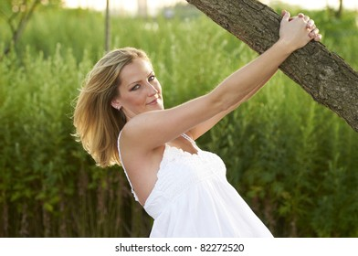 Beautiful blond model wearing white sundress hanging from limb of tree in lush meadow on summer day.
