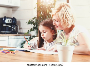 Beautiful blond mother and cute brunette little daughter drawing with color pencils on the light kitchen