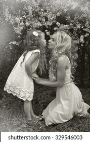 A beautiful blond mother with a small daughter girl snuggling on nature background of green and purple flowers and colorful soap bubbles May, the head wreaths of wild flowers