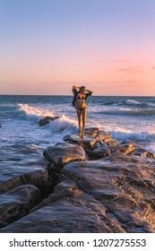 beautiful blond on rocks by the ocean