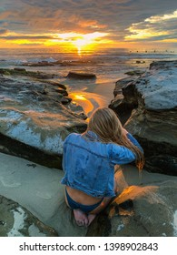 beautiful blond photographing sunset on the coast
