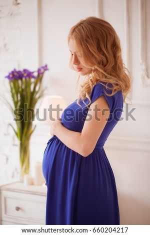 9d18b9e7979 Beautiful blond pregnant woman in a blue dress stroking her belly in a  white room