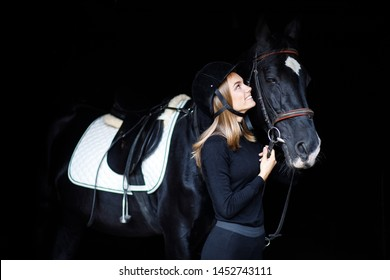 beautiful blond professional female jockey standing near horse. woman horse rider is preparing to equitation. girl and horse. equestrian sport concept. riding vacation. friendship with horse