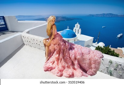 Beautiful blond runaway bride in white wedding dress fabulous with a very long train of crystals in the street on Santorini in Greece.