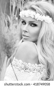 Beautiful blond sexy woman model girl stands on a meadow midst of dried reeds in a beautiful long gauzy white lace dress on the head is a wreath of flowers and sensual glances