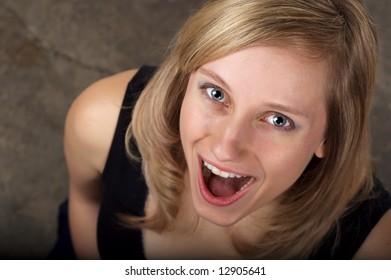 Beautiful blond with a surprised look on her face, dark background