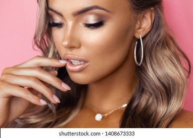 Beautiful blond tanned woman with wavy hair posing on pink backround wearing diamond accessories