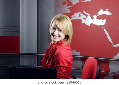 Beautiful blond Television Presenter in front of the laptop looking at the camera