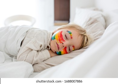 Beautiful blond toddler boy with rainbow painted on his face and messy hands, sleeping in his bed