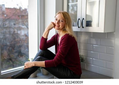 Beautiful blond woman 30-40 years old sitting by the window and smiling