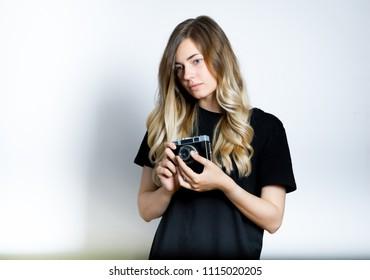 beautiful blond woman adjusting retro camera, isolated studio photo on background