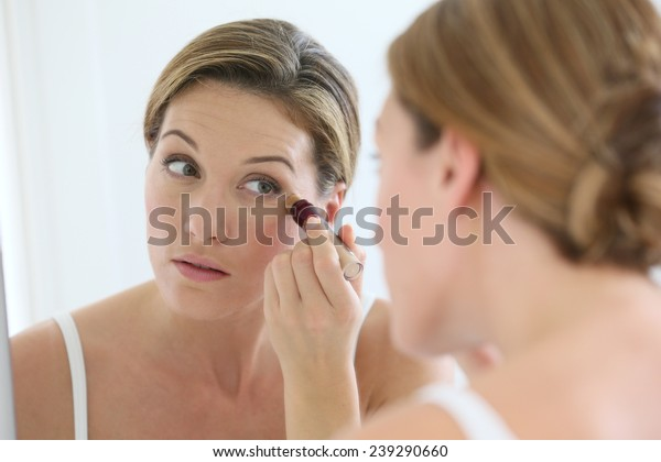 Beautiful blond woman applying concealer around eyes