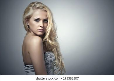 Beautiful Blond woman. Beauty Blond Girl. Pose Model. Make-up. Grey Background