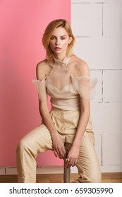 Beautiful blond woman in beige top and beige pants sits on a chair on a pink background.