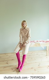 A beautiful blond woman in a beige trench coat, pink tights and pink shoes sits sitting on  a wooden table