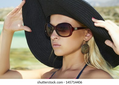 Beautiful blond woman in black hat on a beach