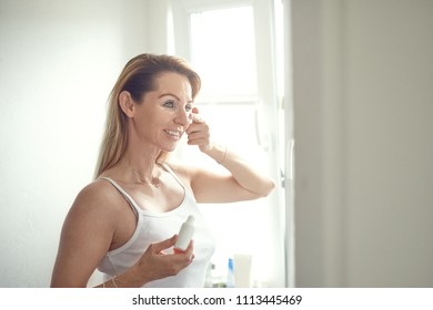 Beautiful blond woman in blue jeans and white shirt standing in home bathroom and applying face cream under her eyes, looking at camera and smiling