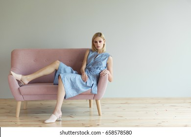 Beautiful blond woman in blue overalls in a light pink shoes sitting on a pink sofa.