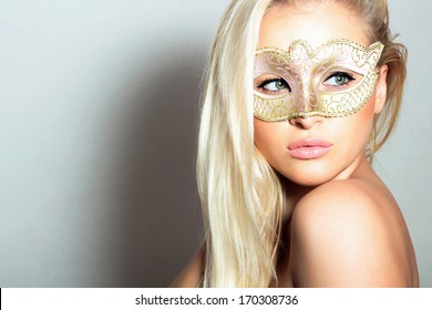 Beautiful Blond Woman in a Carnival Mask.Holiday Masquerade. Sexy Girl. Beauty & Fashion