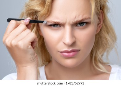 Beautiful blond woman with curly hair having Permanent Make-up Tattoo on her Eyebrows. She holds eyebrow tweezers in her hand. Professional makeup and cosmetology skin care.