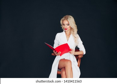beautiful blond woman doctor or health worker in white lab coat, red lips sits and holds a red folder in hands on a black background isolated. copy space text blank