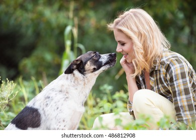 Beautiful blond woman with dog in green garden