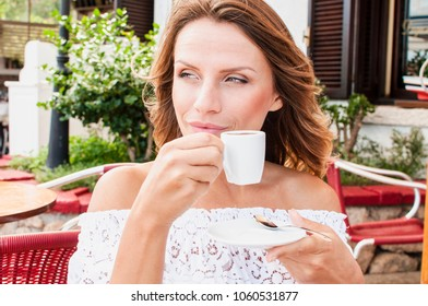 Beautiful blond woman drinking coffee in Italy