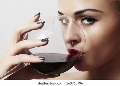 Beautiful blond woman drinking red wine.make-up.red lips.wineglass