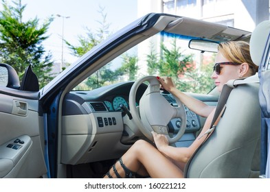 Beautiful blond woman driving her convertible car