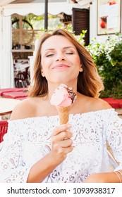 "Beautiful blond woman eat Italian ice cream ""gelato"". Summer concept, happiness, life style, tourism"