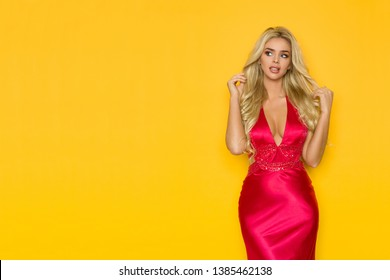 Beautiful blond woman in elegant red dress is looking away at copy space. Three quarter length studio shot on yellow background.