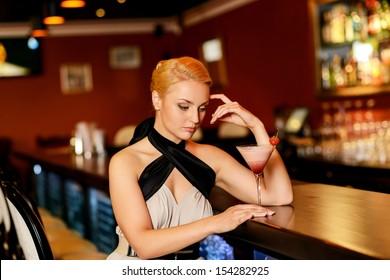 Beautiful blond woman in evening dress sitting near bar counter