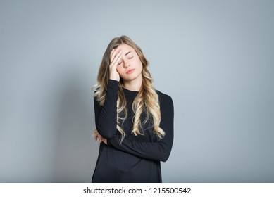 beautiful blond woman feels bad, ill, isolated over black background