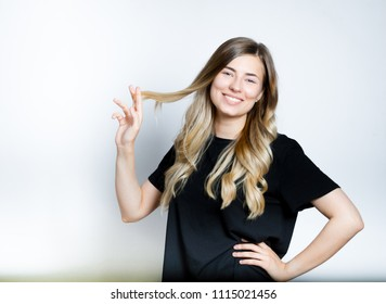 beautiful blond woman with fingers cuts hair, hairdresser, new haircut, isolated studio photo on background